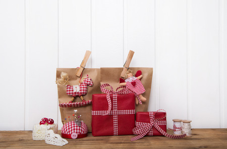 tinkered: Handmade christmas presents wrapped in red paper with checked ribbon on wooden white background.