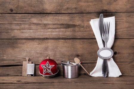 servilletas: Wooden brown christmas holiday background with cutlery and a white napkin for decoration with a red ball.