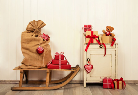 Christmas gift boxes in red and white vintage style on old wooden background with sledge. Stok Fotoğraf