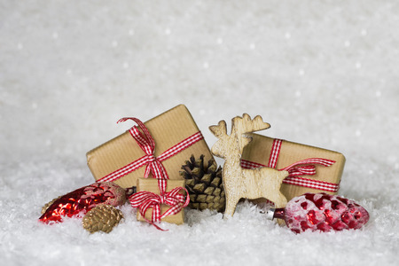 craft material tinker: Red white checked presents on snowy background with wooden reindeer. Stock Photo