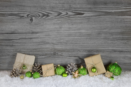 xmas background: Green Christmas presents wrapped in natural paper on old wooden grey country background.