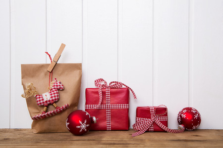 Handmade christmas presents wrapped in paper with red white checked ribbon and a hanging rocking horse. Stok Fotoğraf
