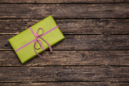 publicity: One green present with checked ribbon on wooden rustic background for publicity.