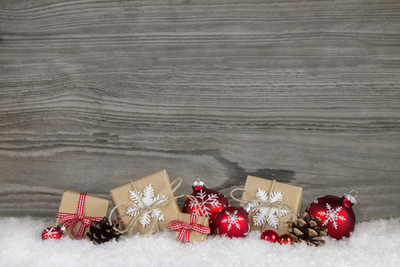 Red Christmas presents wrapped in natural paper on old wooden grey country background. Standard-Bild