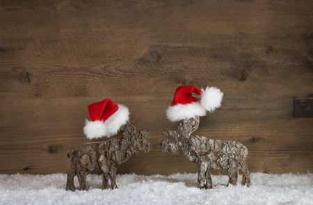 xmas background: Two handmade wooden reindeer with red white santa hats on a snowy background for xmas decoration.