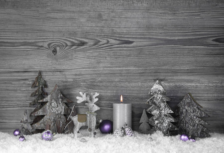 christmas elk: Grey and purple christmas decoration with moose and candle on old wooden background. Stock Photo