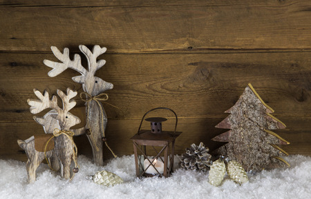 Rustic country style decoration with reindeer, lantern and snow on old wooden background with balls. Stock Photo