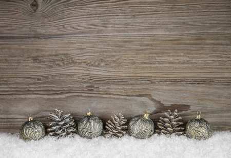 Old antique wooden xmas background with balls and pin corns on snow.