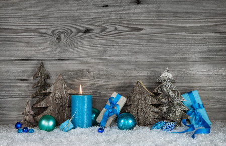 christmas candle: Blue, white and grey Christmas decoration with one candle for the first advent. Stock Photo