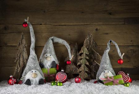 duendes de navidad: la decoración rústica de la Navidad en estilo rústico con IMP como santa en el fondo de madera vieja con los regalos verdes.