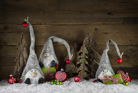 Rustic christmas decoration in country style with imp like santa on old wooden background with green gifts.