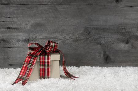 země: Jedna červená kostkovaný Vánoční dárek s mašlí na dřevěné starém šedém pozadí pro dekoraci.