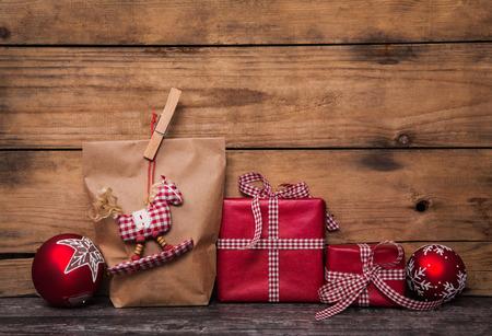 Cadeaux de Noël faits à la main enveloppés dans du papier blanc à carreaux rouges ruban et un cheval à bascule suspendue.