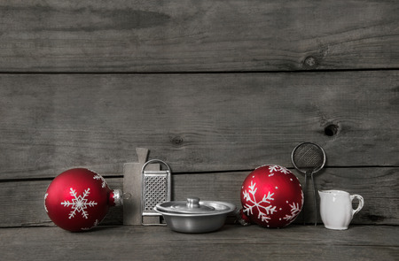christmas cooking: Grey Kitchen Christmas background with red balls and dishes on wood for decoration.k Stock Photo