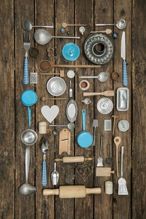 cocina vieja: Antigua decoración del antiguo equipo de cocina con cubiertos y platos de fondo de madera vieja por la gastronomía.