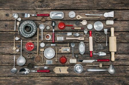 juguetes antiguos: Fondo antiguo de madera con una colección de los niños antiguos juguetes para la cocina. Antecedentes para los conceptos de cocina y de restaurante en rojo, plata y marrón.
