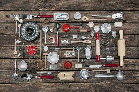 Wooden old background with a collection of old children toys for the kitchen. Background for cooking and restaurant concepts in red, silver and brown colors.