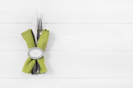 napkin ring: Wooden white background for a menu card fork, knife and a apple green napkin with ring.