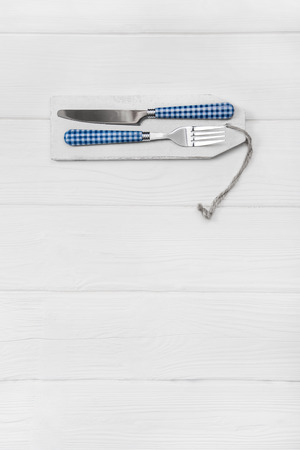 gastronomy: Wooden white background for a menu card with cutlery in blue white checked colors for restaurants and gastronomy placards.