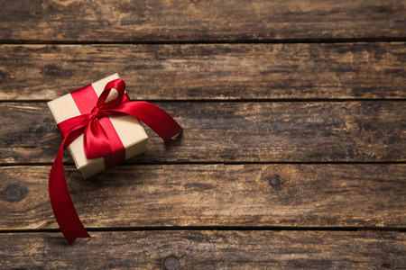 country christmas: One present with an red big ribbon on old wooden dark brown background for christmas. Stock Photo