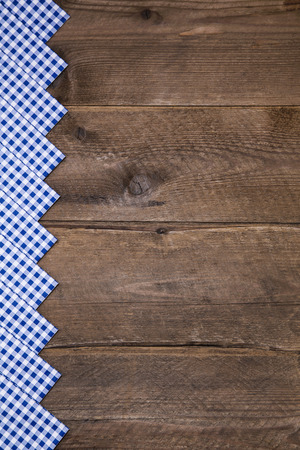 dark blue: Old wooden background with blue and white checked border for bavarian decoration.