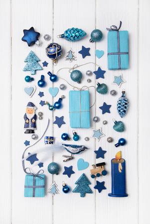 azul turqueza: Colecci�n de miniaturas azules y turquesas con los presentes para la decoraci�n de navidad en el fondo blanco de madera en estilo moderno. Foto de archivo