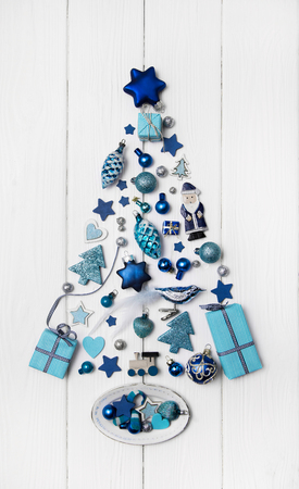 Blue and turquoise christmas tree of small miniatures on white wooden background for decoration in modern style. Standard-Bild