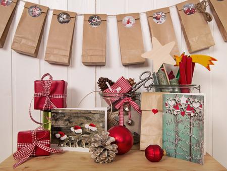 adviento: Regalos de Navidad hechas a mano y calendario de adviento en colores rojo, blanco y verde en estilo rústico. Foto de archivo