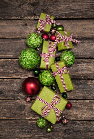 bard: Apple green christmas gift boxes with a red white check ribbon on old wooden bard for decoration.