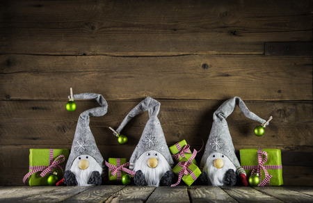Three santa with grey felt hats and apple green christmas presents on an old wooden background for decoration. Stockfoto