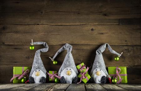 Tři santa s šedou plstěných klobouků a zelené jablko vánoční dárky na staré dřevěné pozadí pro dekorace.