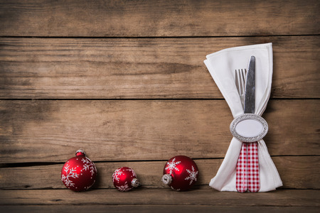 christmas catering: Rustic country style christmas decoration with red white checked cutlery on old wooden brown background.