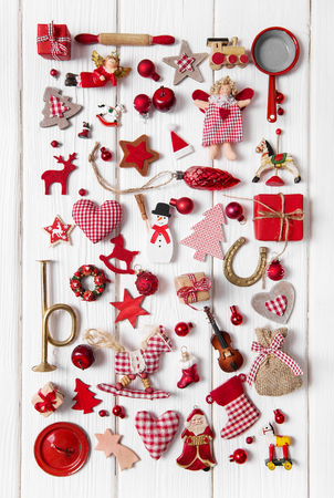 angel figurine: Collection of small red and white checkered christmas decoration on wooden background. Stock Photo