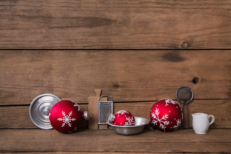 kitchen utensils: Old rustic wooden christmas background with kitchen utensils and red balls for decoration.
