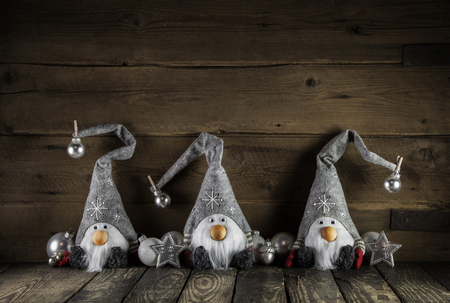 humorously: Three handmade witty santa claus of felt on old wooden background for christmas decoration.