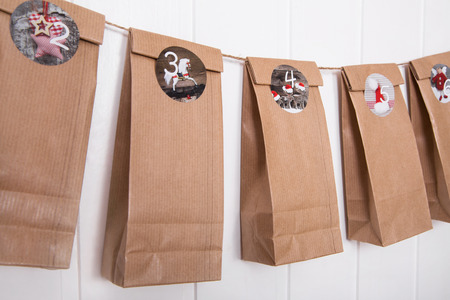 Handmade crafted advent calendar with paper bags and stickers.
