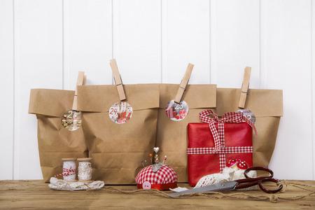 paper craft: Regalos de Navidad vanamente envueltos en bolsas de papel con clips de madera en colores rojos y blancos con fuentes de costura. Foto de archivo