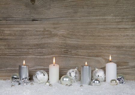 chic: Four burning advent candles on brown wooden background for christmas decoration in shabby chic style.
