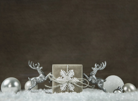 wooden reindeer: Wooden shabby chic christmas background in silver, white, brown and grey colors with gift box and reindeer.