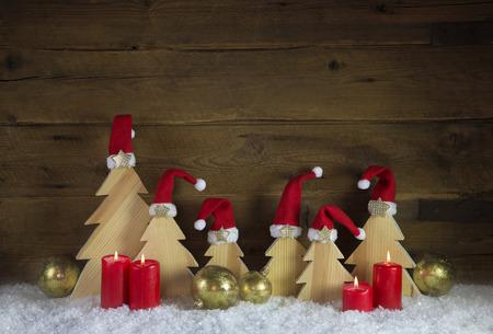 luz roja: Cuatro rojos ardientes velas del advenimiento con los árboles de navidad en el fondo cubierto de nieve tallados de madera para las decoraciones. Foto de archivo