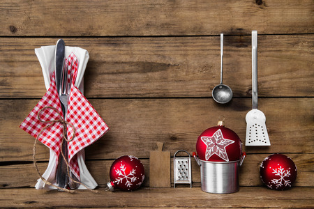 gastronomy: Dinner on christmas. Old wooden background with red white checked cutlery and dishes for decoration. Stock Photo