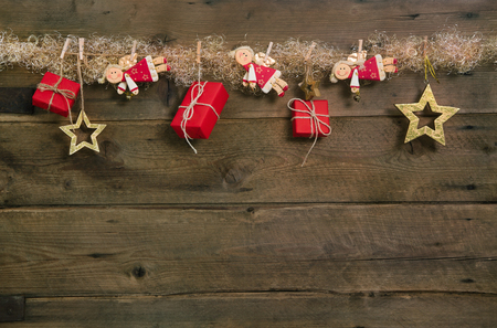 Rustic country style christmas background with red gift boxes and hanging angels.