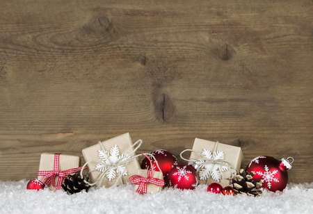 Red Christmas presents wrapped in natural paper on old wooden grey background.