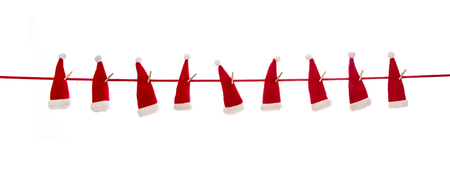 Isolated hanging red santa or nicholas hats over white background. Imagens