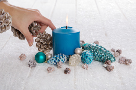 Woman decorating christmas in blue, white and brown colors with candlelight.