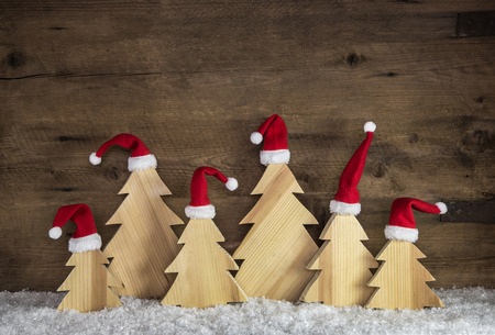 Witty wooden christmas background with trees and santa hats on snow.