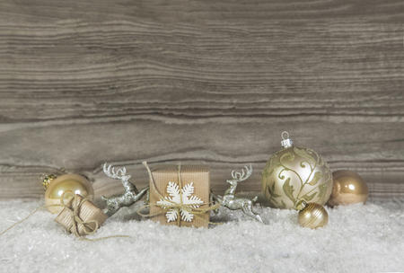 Wooden background with christmas decoration in gold, silver and white colors.
