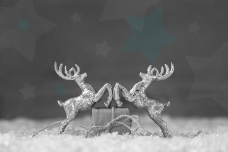 Two silver reindeer figurine on grey shabby style christmas background. Imagens
