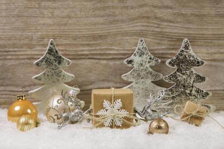 Argent, or, décoration de Noël blanc et brun avec une bougie allumée sur fond de bois.