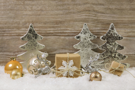 Silver, gold, white and brown christmas decoration with one burning candle on wooden background.